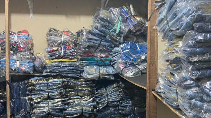 Polícia apreende máquinas utilizadas na confecção de roupas falsificadas e três pessoas são detidas